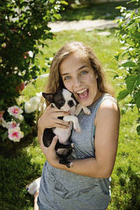 Portrait happy teenage girl holding Boston Terrier puppy in sunny garden