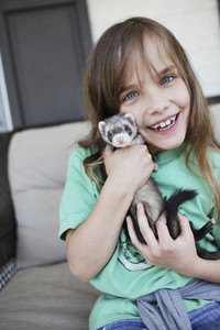 Portrait happy girl holding baby ferret