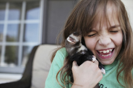 Happy girl laughing and holding baby ferret