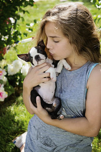 Teenage girl holding and kissing Boston Terrier puppy in sunny garden