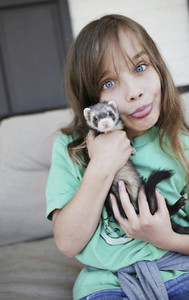 Portrait silly girl holding baby ferret and making a face