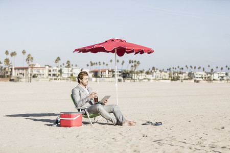 Businessman with digital tablet working on sunny beach
