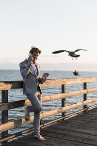 Barefoot businessman talking on smart phone on sunny pier