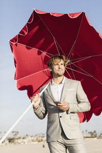 Businessman with beach umbrella on sunny beach