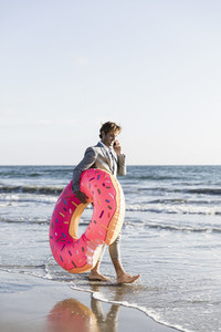 Businessman with inflatable donut on sunny ocean beach