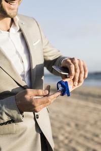 Businessman applying sunscreen on sunny beach