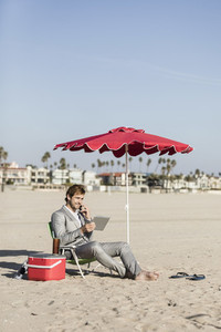 Barefoot businessman with smart phone and digital tablet working on beach