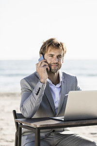 Businessman with smart phone and laptop working on sunny beach