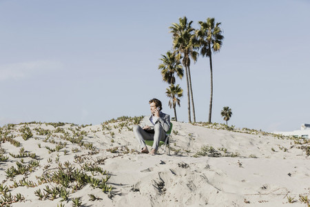 Businessman talking on smart phone on sunny beach