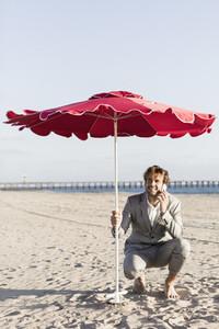 Businessman talking on smart phone under beach umbrella on sunny beach