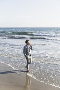 Barefoot businessman talking on smart phone in sunny ocean surf