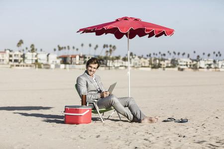Portrait happy barefoot businessman working on sunny beach
