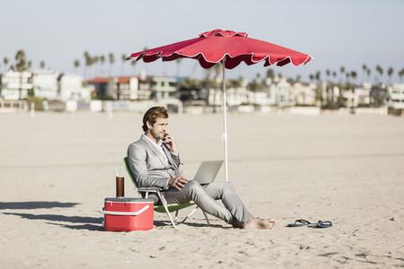 Barefoot businessman working on sunny beach