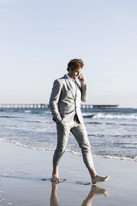 Barefoot businessman walking on sunny ocean beach