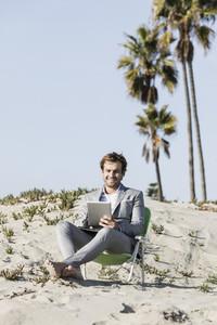 Barefoot businessman using digital tablet on sunny beach