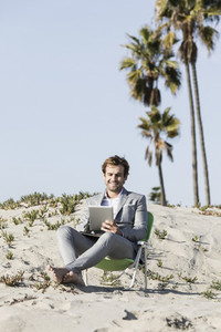 Barefoot businessman using digital tablet on sunny beach