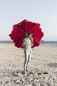 Barefoot businessman with beach umbrella on sunny beach