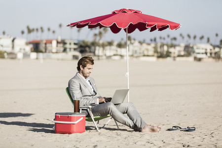 Barefoot businessman using laptop on sunny beach Los Angeles