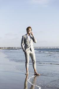 Barefoot businessman talking on smart phone on sunny ocean beach