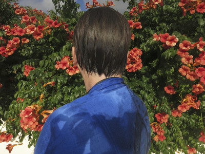 Woman with wet hair standing at flowers in sunny garden