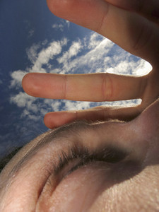 Close up woman shielding eyes with hand under sunny sky