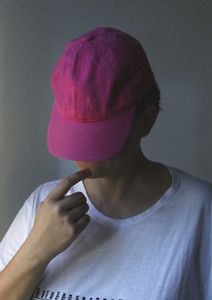 Pink baseball cap obscuring face of woman with hand on chin