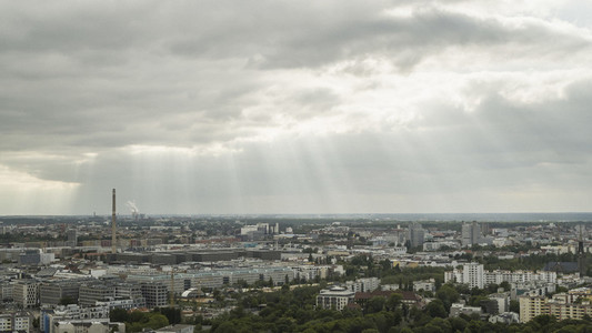 Sunbeams in clouds over Berlin cityscape