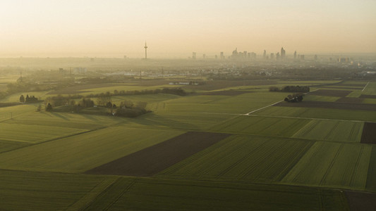 Scenic view rural farmland and Frankfurt cityscape at sunset