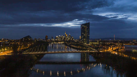Illuminated Frankfurt cityscape and Osthafenbruecke bridge at night