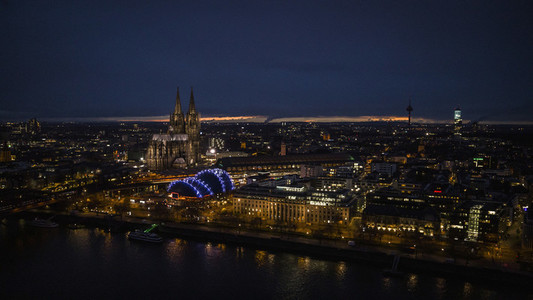 Illuminated Cologne Cathedral and cityscape at night