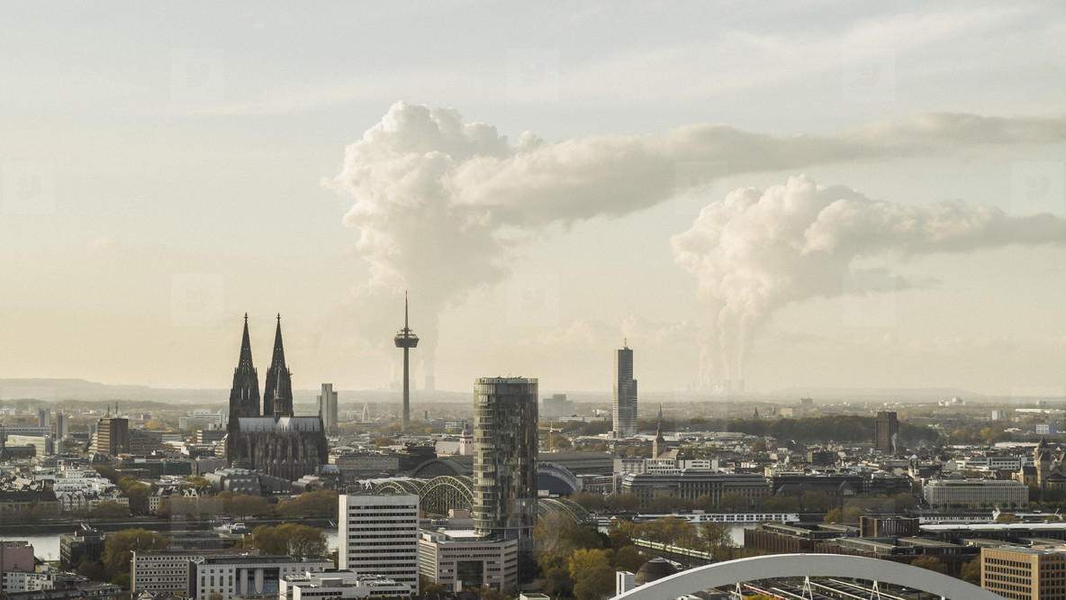 Smoke rising from factories behind Cologne cityscape