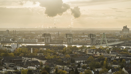 Smoke rising from factory behind Cologne cityscape