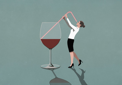 Businesswoman drinking from large wine glass with straw
