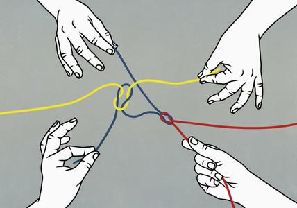 Hands pulling tangled strings