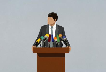 Politician speaking at microphones on podium