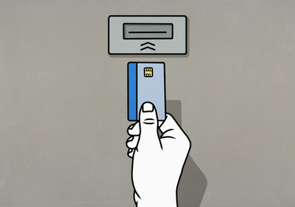 Hand inserting chip credit card into ATM