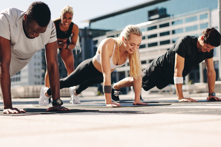 Group of people doing push ups outdoors