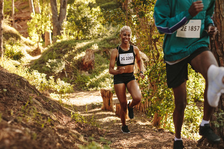 Smiling marathoner running uphill