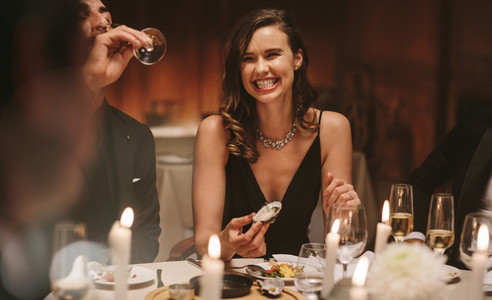 Pretty woman enjoying dinner party with friends