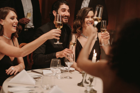 Group of friends toasting champagne at dinner party
