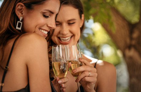 Best friends at party toasting champagne