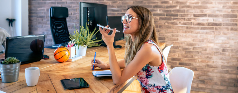 Office worker talking mobile phone with speaker