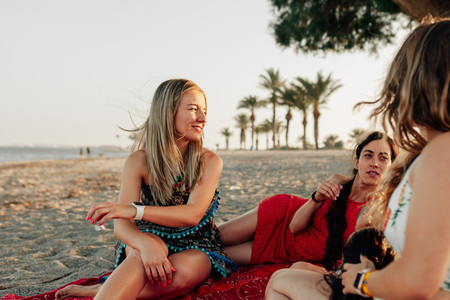 Young women lying on beach  smiling and talking over big scarf