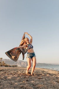 Woman running and holding scarf on wave relax and happy on beach