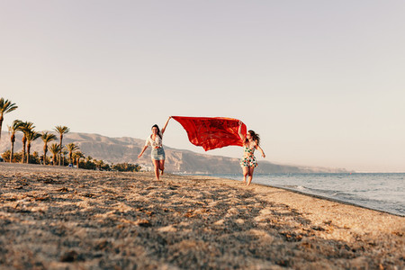 Two women running and holding scarf on wave relax and happy on beach
