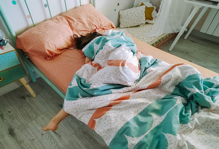 Girl sleeping covered up in her bed