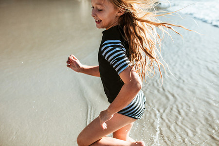 Girl running in water at the beach