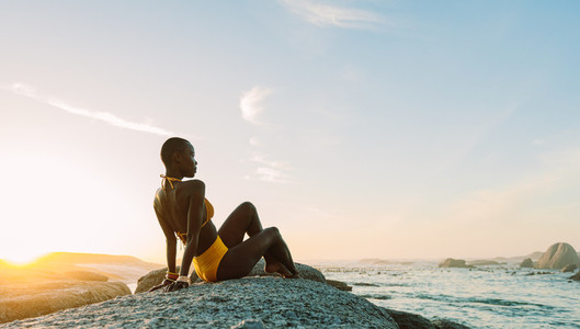 African woman relaxing on a rock at the beach