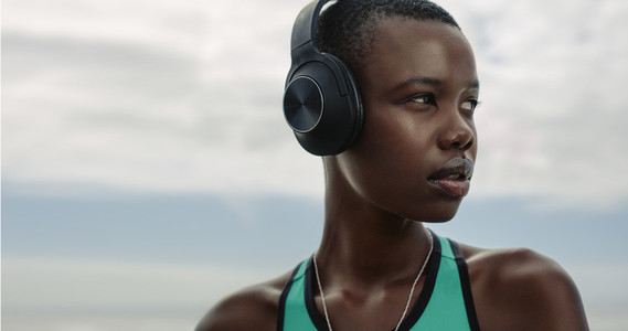 Sporty woman with headphones standing outdoors
