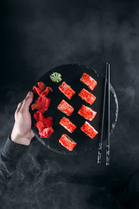 sushi california on a black stone board on a background of smoke